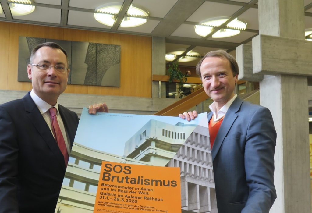 """""""SOS Brutalismus"""": OBM Thilo Rentschler und Kurator Oliver Elser (rechts) mit dem Ausstellungsplakat im Aalener Rathaus (Quelle: Andreas Erb)"""